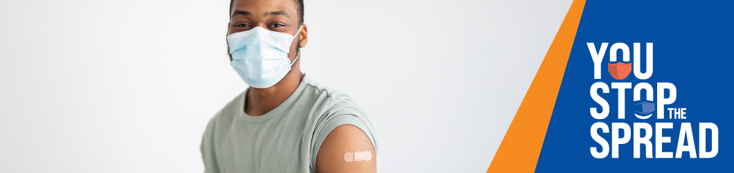 A young adult wearing a mask with a band-aid on their arm