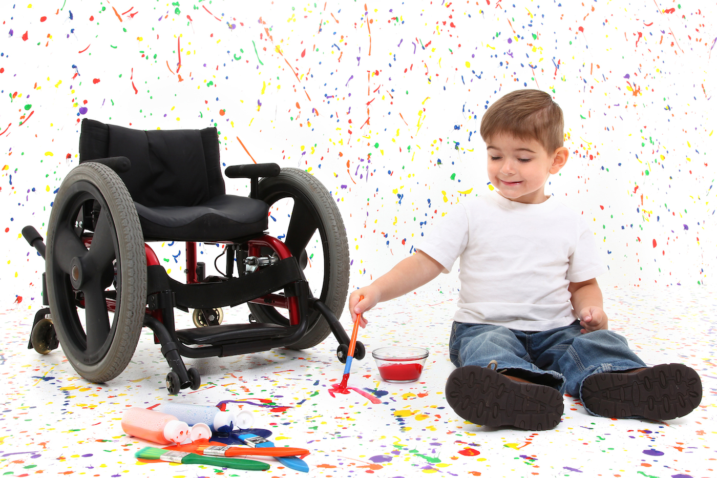 Child in wheelchair splatters paint in a white room