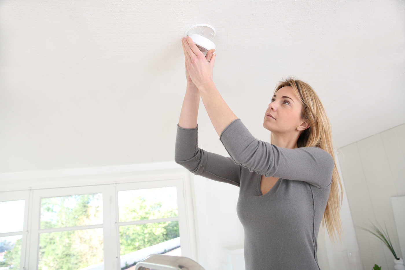 Woman installing a fire alarm