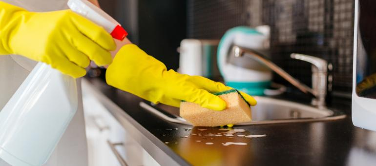 Hands holding spray bottle and a sponge while cleaning a countertop