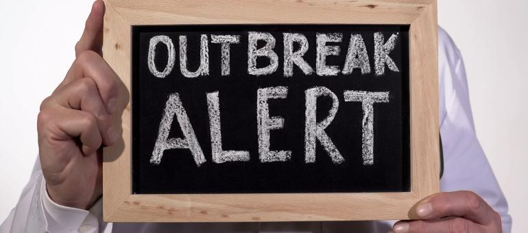 Close up of an adult holding a chalkboard with the words Outbreak Alert
