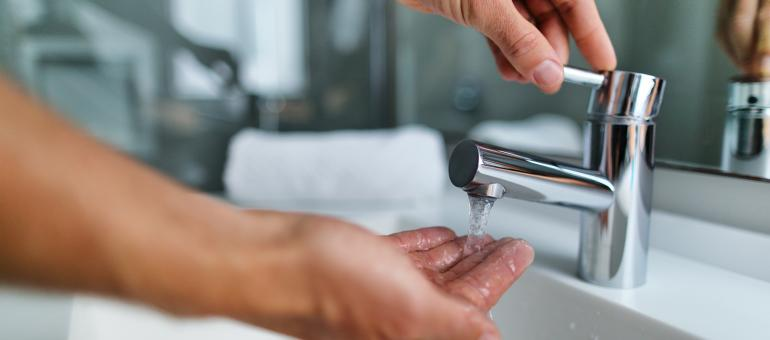Close up of adult washing hands at sink