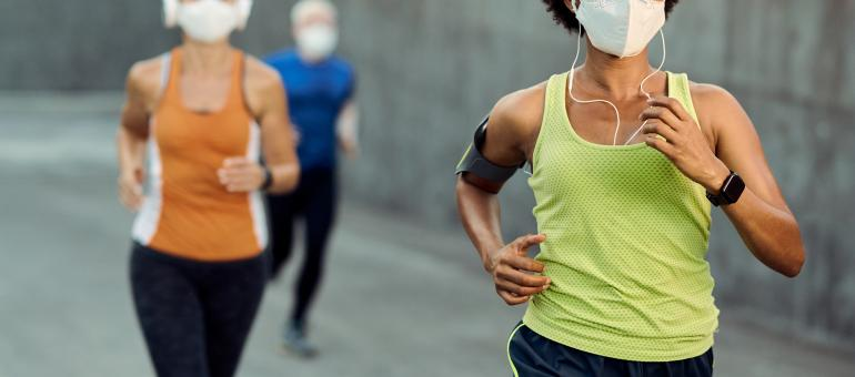 Adults wearing masks while jogging
