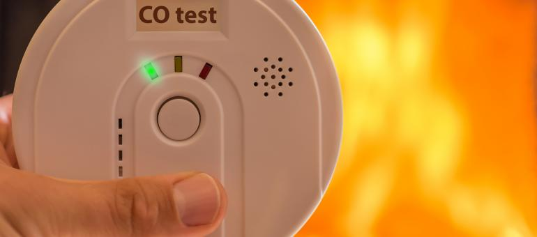 Close up of hands holding a carbon monoxide alarm with a blurred fire background