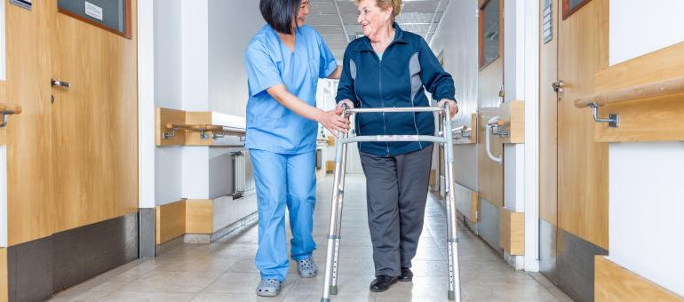 Nurse assisting a senior use a walker down a hospital hallway