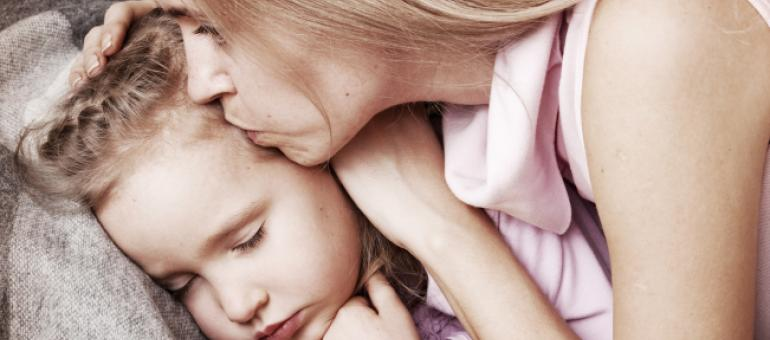 Mother kissing sleeping child
