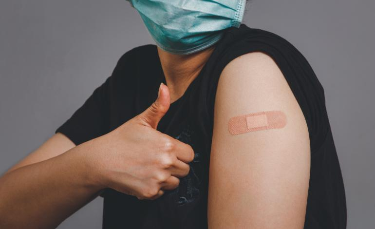 Close up of an adult giving a thumbs up, wearing a mask with a band-aid on a vaccine site