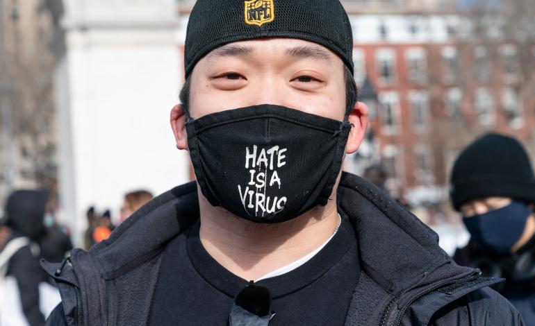 Close up of an adult wearing a mask with 'Hate is a Virus' on the front at a rally