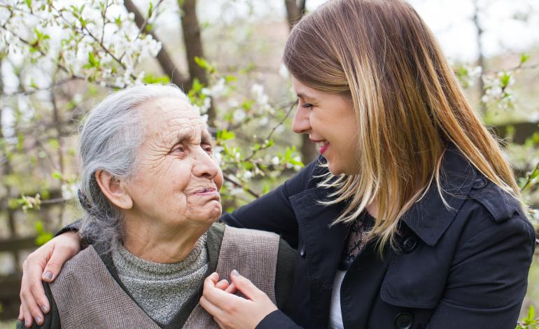 Young adult caregiver with senior outdoors