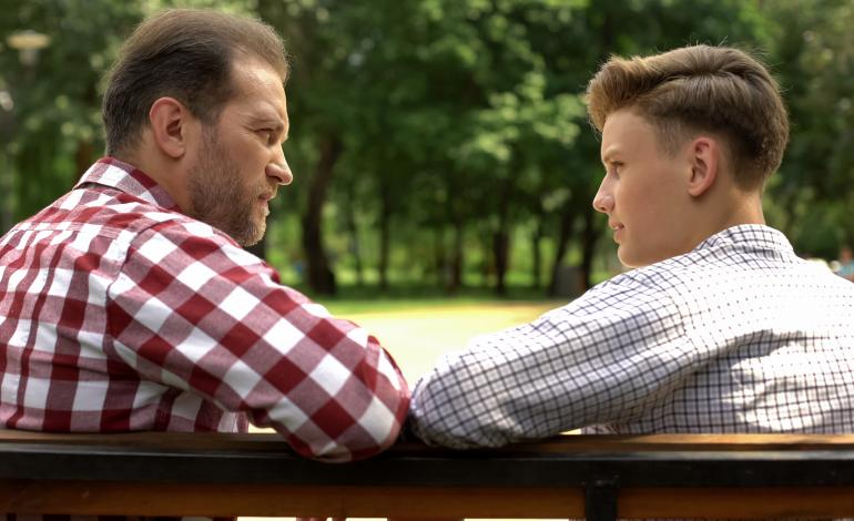 An adult and a teen sitting on a bench talking