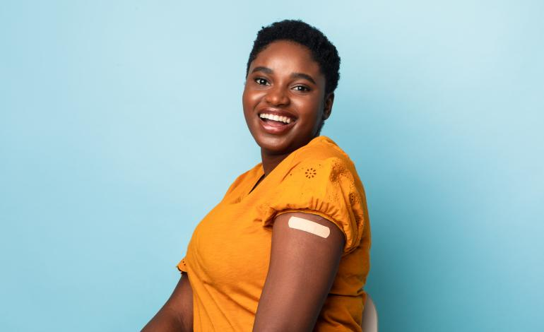 A smiling adult with sleeve rolled up showing band aid covered vaccine spot