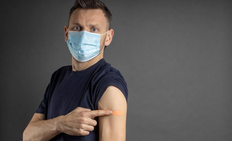 A masked adult with sleeve rolled up pointing to his vaccinated arm