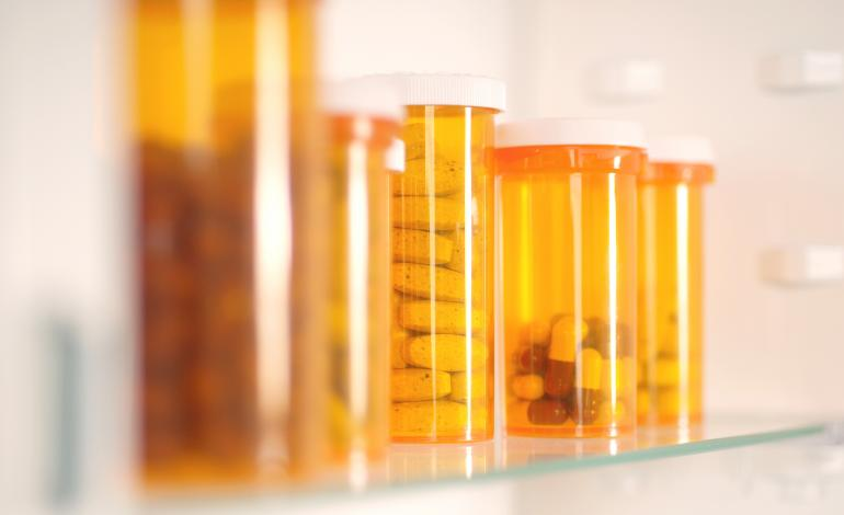 A row of medications in bottles on a shelf