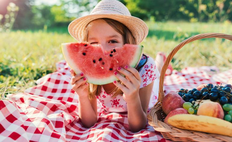Child laying on a checked tablecloth outdoors eating watermelon