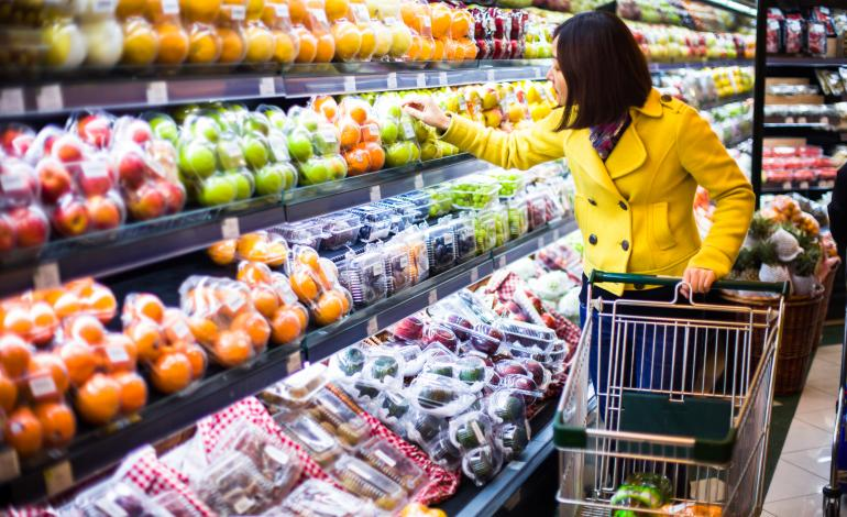 An adult choosing a produce in the fruit aisle at a supermarket