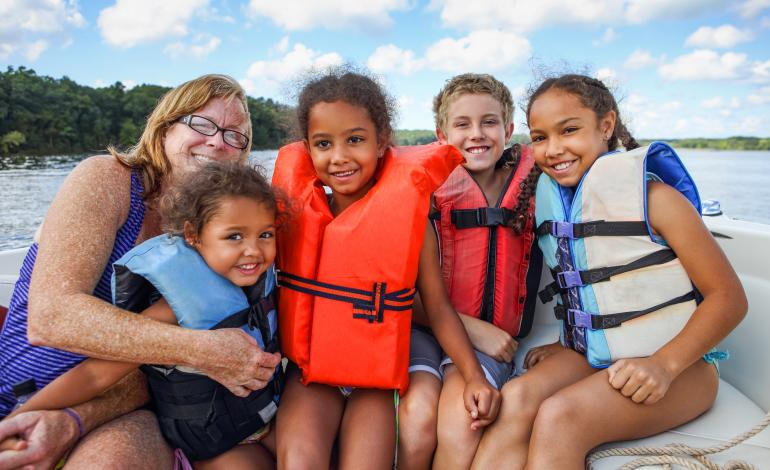 Smiling family sitting in boat wearing life vests