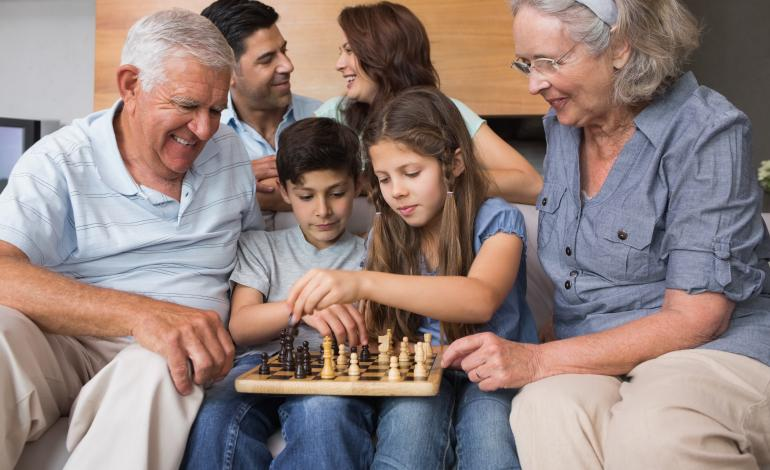 Multigenerational family playing chess