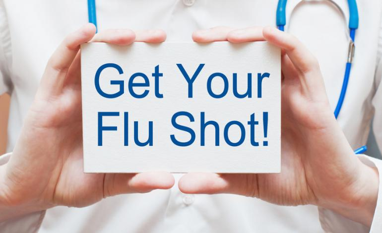 Medical staff's hands holding a sign saying get your flu shot!