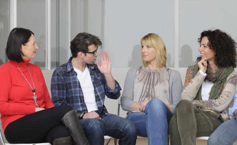 Four adults sitting in a circle, talking