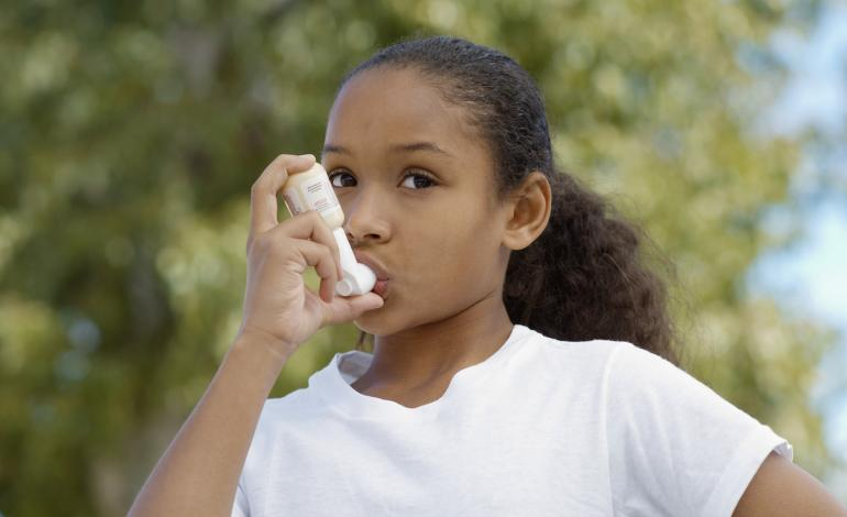 A child uses an inhaler outside