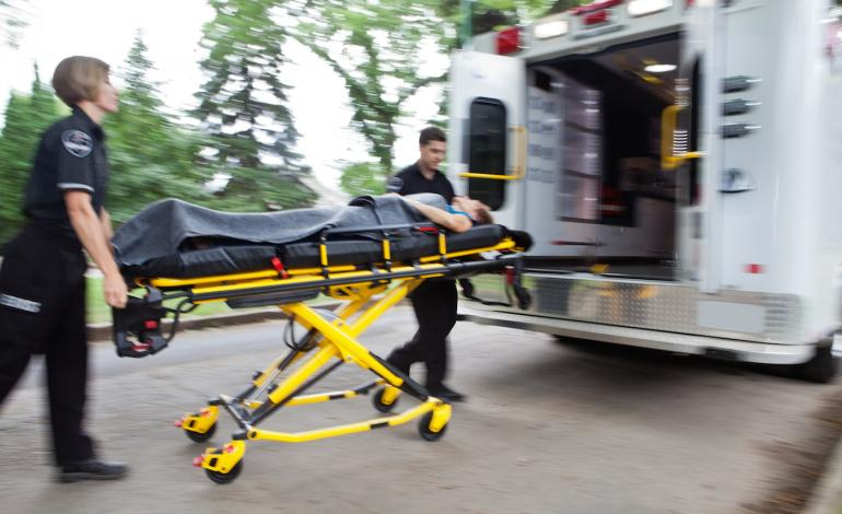 EMTs transporting a patient on a backboard