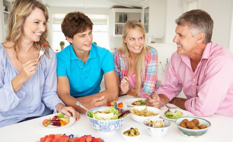 Family stands around table at meal time