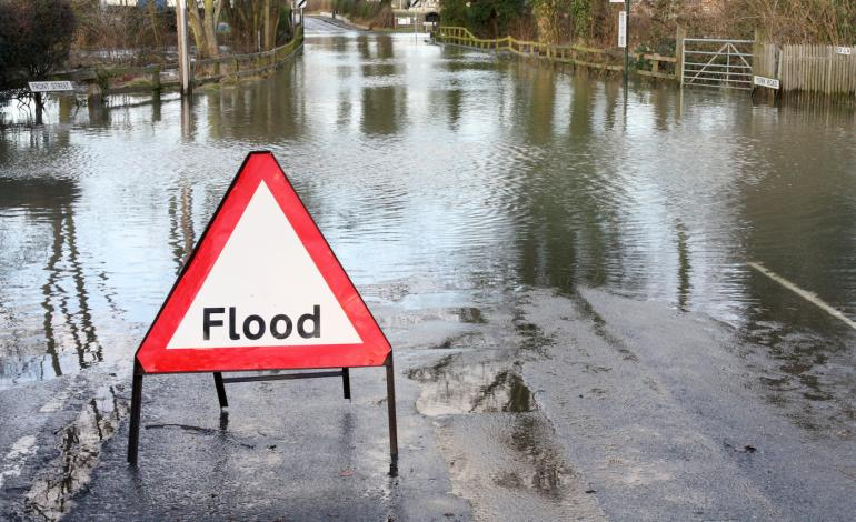 A white triangle with red trim sign, flood, set on flooded road