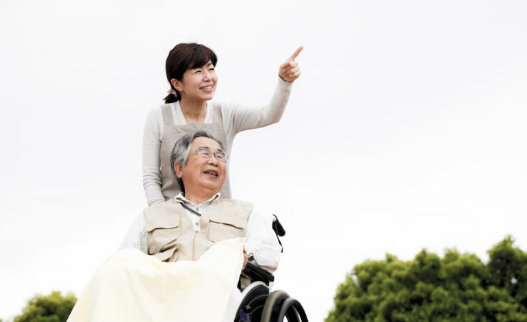 Woman pushing elderly man seated in wheelchair
