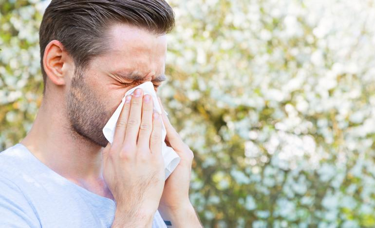 An adult blows nose outside.