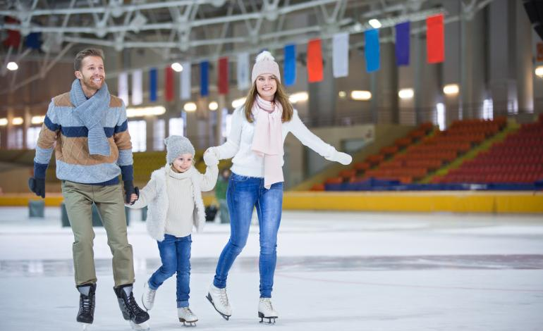 A child between two adults ice skating on an indoor rink.