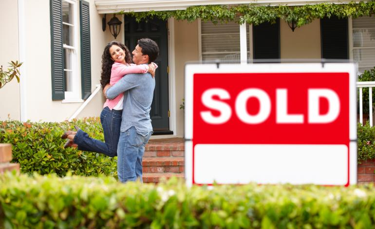 """Happy couple hugging front of their new home with a sign """"sold"""" in the front."""