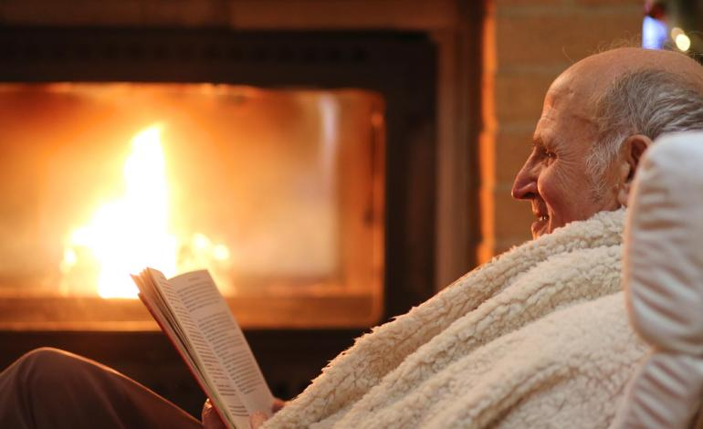 Elderly man enjoys reading a book while lounging by a fireplace