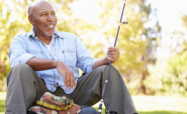 A grinning adult sitting down with a fishing rod.
