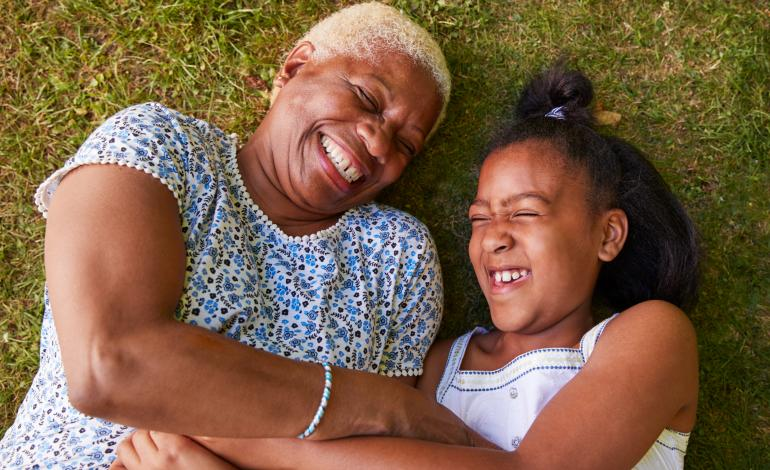 Senior and young girl lying on the grass laughing together
