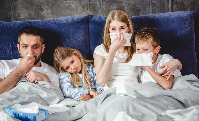 Sick family in bed blowing noses