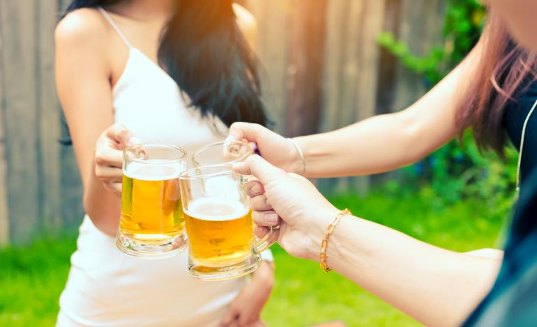 Three young women toasting with beer mugs