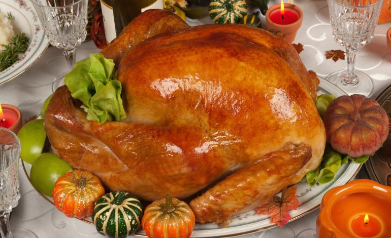 A roasted turkey on a plate surrounded with small pumpkins