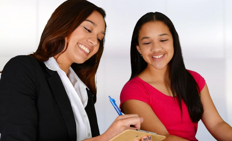 Image of two smiling women, one of them holding a clipboard.