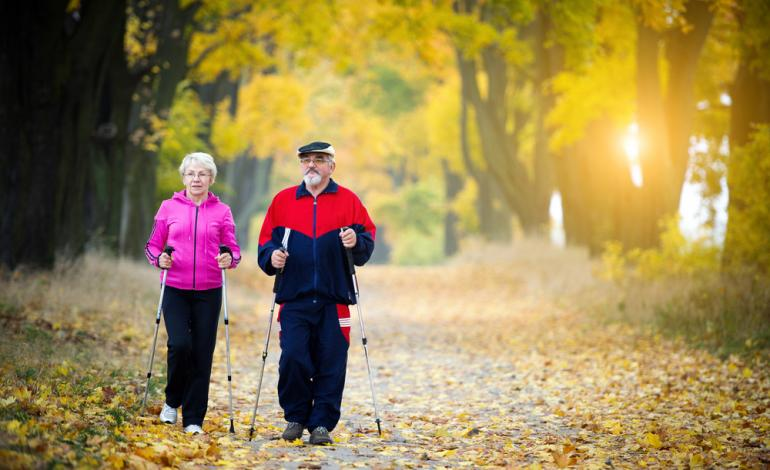 A pair of seniors take a stroll on an autumn day.