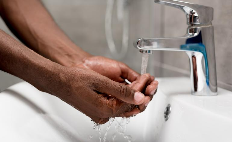 Washing hands under a faucet.