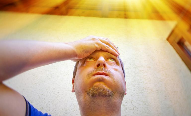 Man in discomfort holding head while sun beats down