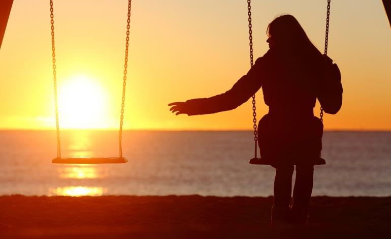 A silhouette of an adult on swing reaching out to an empty swing.