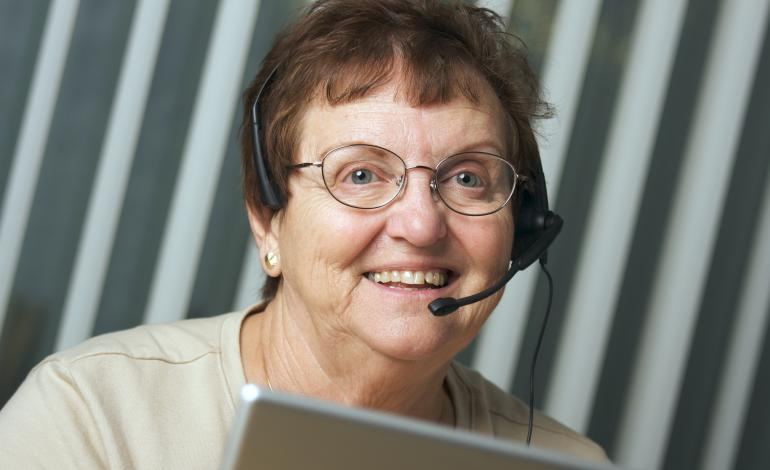 A smiling adult with headset