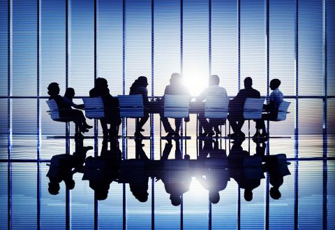 Silhouette of people at a business meeting against a backdrop of windows with sun shining