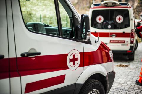 Two ambulances with red cross emblem on the passenger doors.