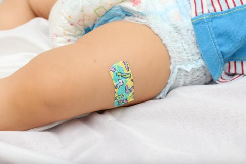 A bandage on a baby's leg.