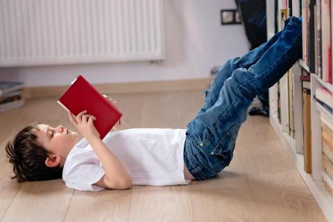 A child reads a book with his feet up on a bookcase