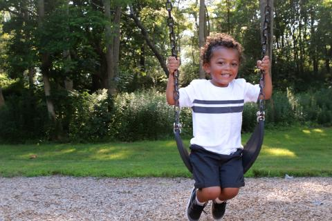Young African American boy on swing