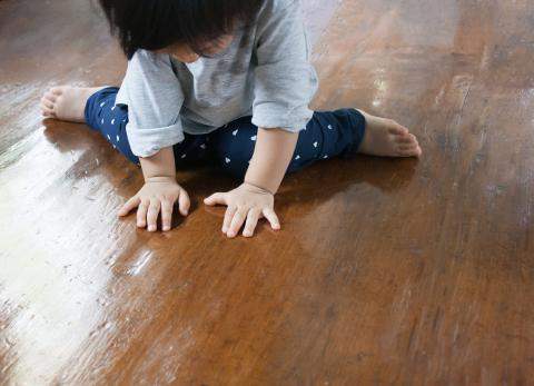 A toddler examining the wood floor