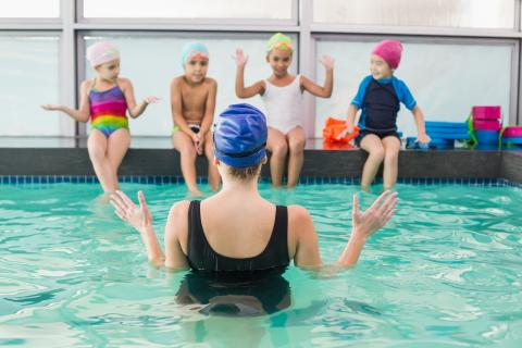 An instructor explaining to four young children sitting on the edge of a swimming pool.